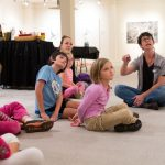 Family workshop participants learn about artwork in the exhibition Threatening Beauty